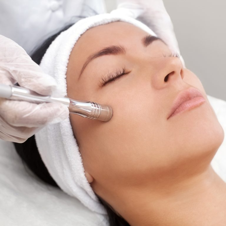 Woman receiving an acne removal facial treatment from a specialist.