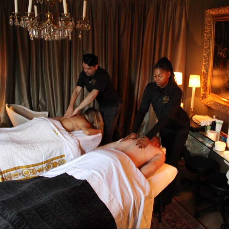 Couple experiencing romantic, relaxing couples massage from two therapists.