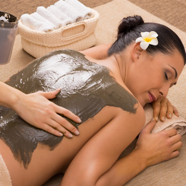Massage therapist applying mineral wrap to a woman's back.