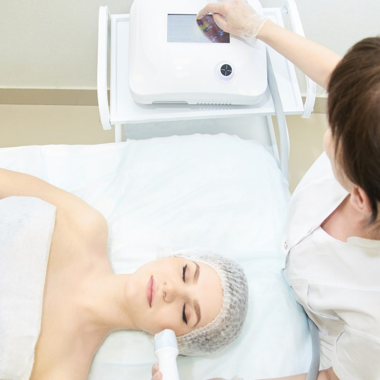 Resting woman receiving endermolift treatment from a technician.