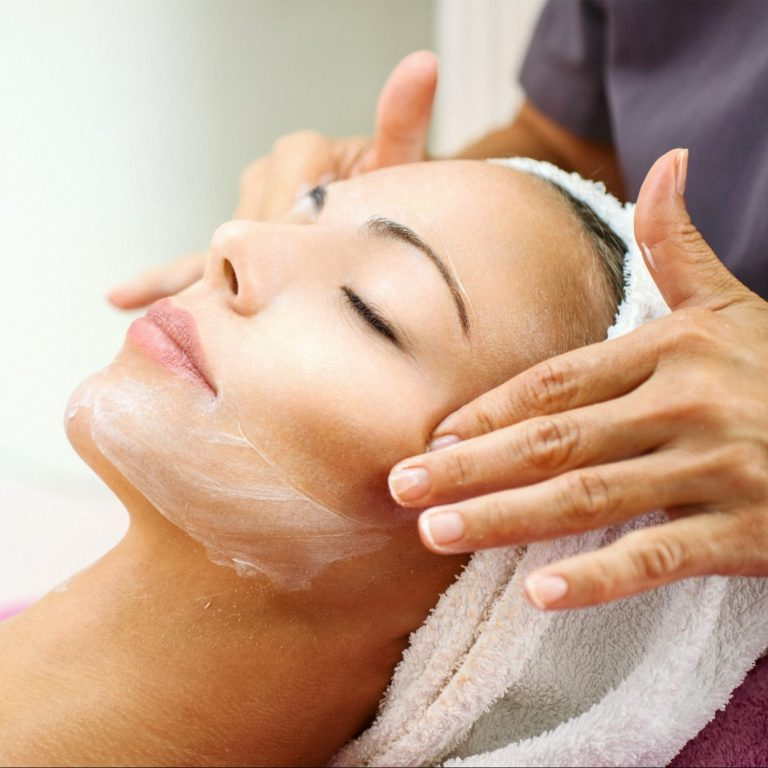 Woman receiving a facial massage from a specialist.