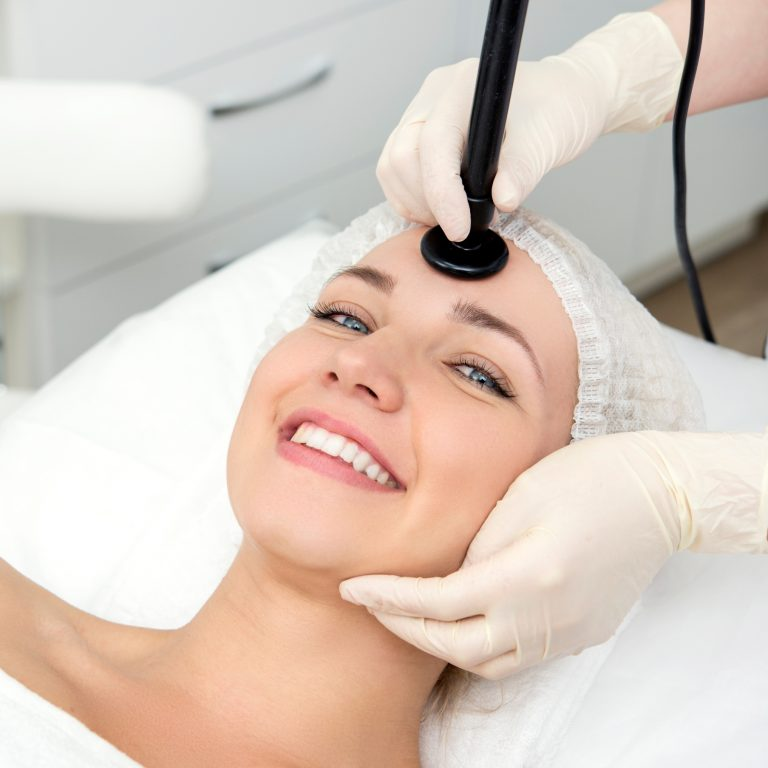 Woman smiling as she receives anti-aging treatment from a medical specialist.