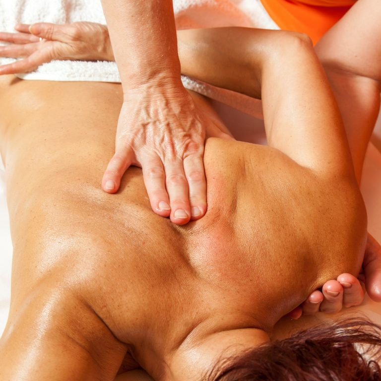 A therapist massaging lymphatic trigger points on a woman's back.