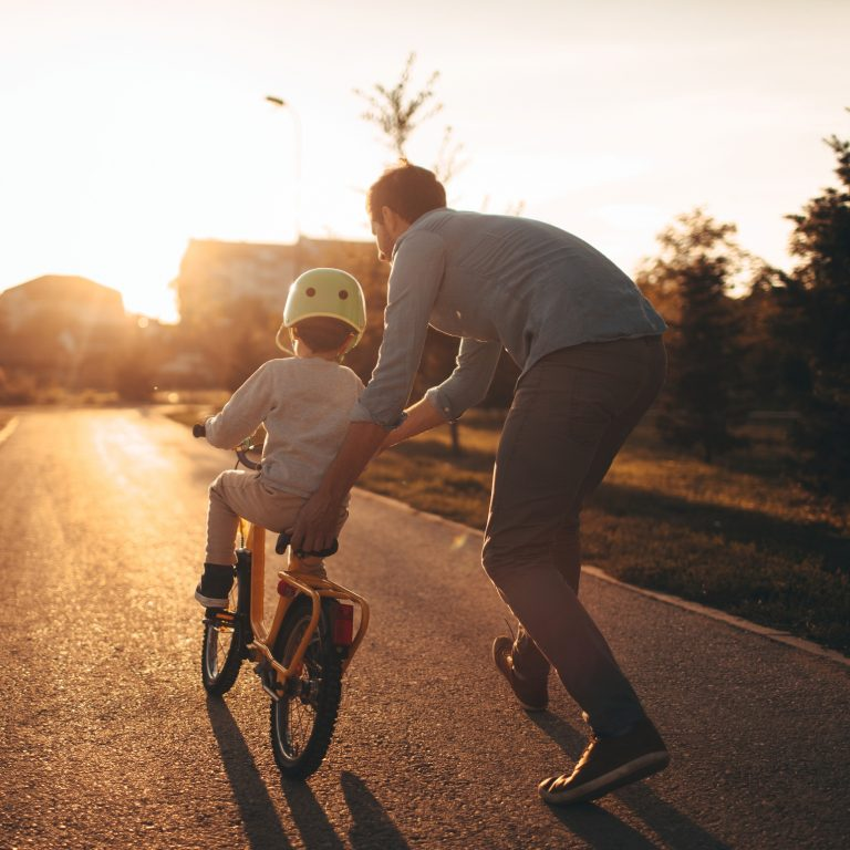 Suburban father helping son ride bicycle against a setting sun.