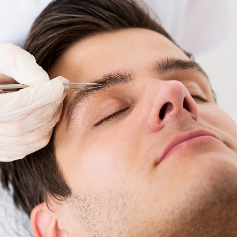 Resting man having his eyebrows tweezed by a specialist.