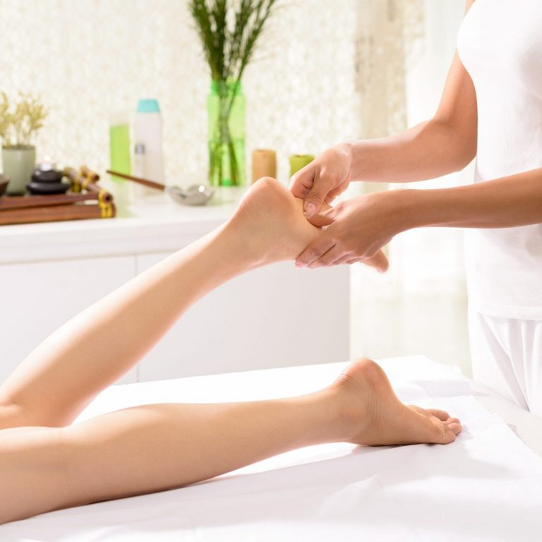 A therapist applying pressure to specific points on a woman's foot.