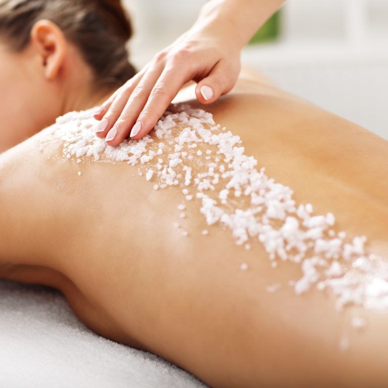 Woman having sea salt layered and scrubbed over her back by a therapist.