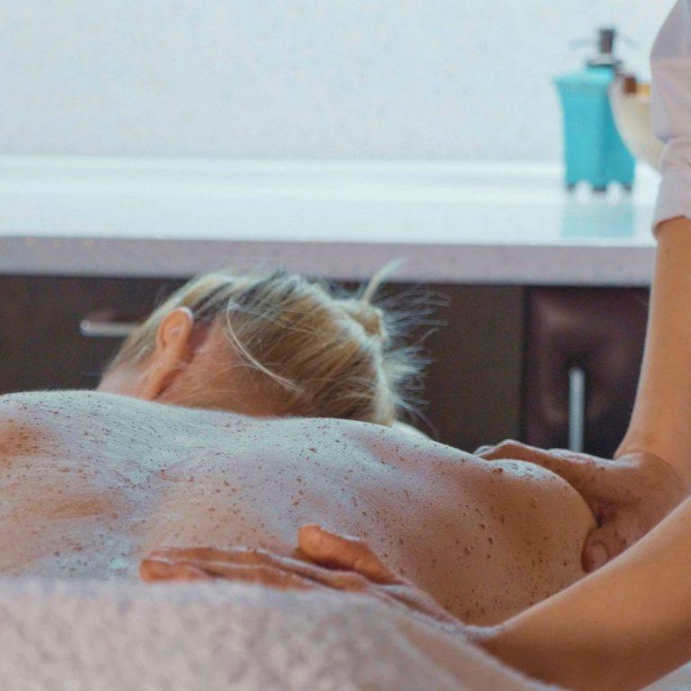 Applying sugar scrub to cleanse and exfoliate skin