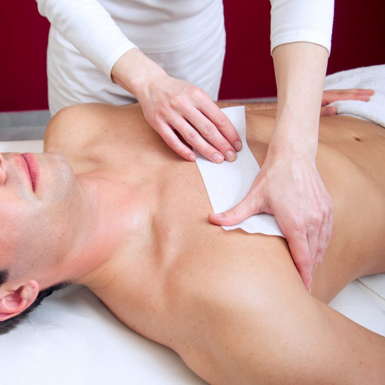 Therapist applying a wax strip to a man's chest.